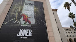 """A poster for the upcoming film """"The Joker"""" is seen outside Warner Brothers Studios in Burbank, California, September 27, 2019. - The Los Angeles Police Department said Friday it plans to step up its visibility around movie theaters for the opening of """"Joker"""" because of heightened fears over the film's content."""