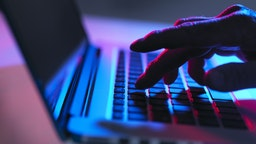 Silhouette of male hand typing on laptop keyboard at night.