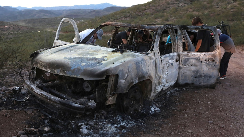 """Members of the Lebaron family watch the burned car where part of the nine murdered members of the family were killed and burned during an gunmen ambush on Bavispe, Sonora mountains, Mexico, on November 5, 2019. - US President Donald Trump offered Tuesday to help Mexico """"wage war"""" on its cartels after three women and six children from an American Mormon community were murdered in an area notorious for drug traffickers."""