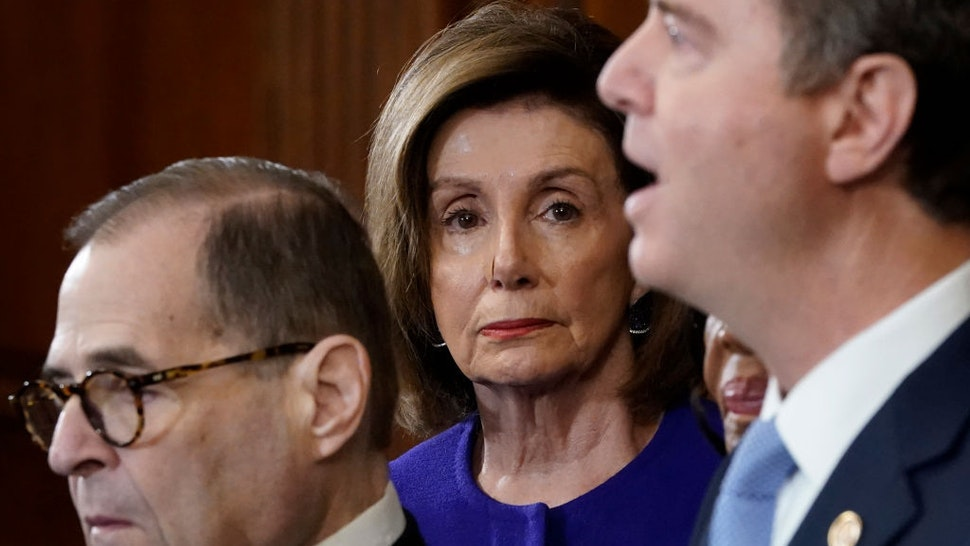 """Speaker of the House Nancy Pelosi (D-CA) (C) listens as House investigative committee chairs Rep. Adam Schiff (R) (D-CA) and Rep. Jerry Nadler (L) (D-NY) announce the next steps in the House impeachment inquiry at the U.S. Capitol December 10, 2019 in Washington, DC. The impeachment charges include abuse of power and obstruction claims and """"clear and present danger"""" to national security and the 2020 election. (Photo by Win McNamee/Getty Images)"""