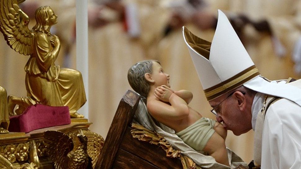 Pope Francis kisses the unveiled baby Jesus during a Christmas Eve mass at St Peter's Basilica to mark the nativity of Jesus Christ, on December 24, 2014 at the Vatican.