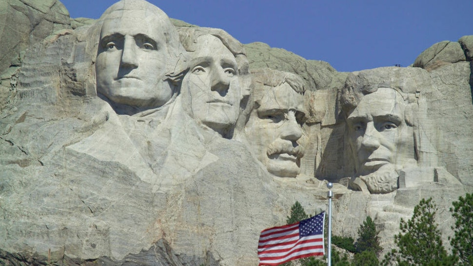 The faces of American Presidents George Washington, Thomas Jefferson, Theodore Roosevelt e Abraham Lincoln carved in the granite, American flag in the foreground, Mount Rushmore National Memorial, South Dakota, United States of America.