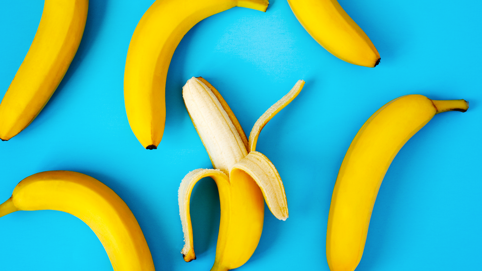 Ripe bananas on blue background, flat lay.
