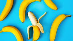 Ripe bananas on blue background, flat lay.