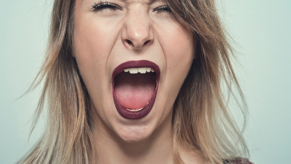 Close-uo of Young woman screaming.