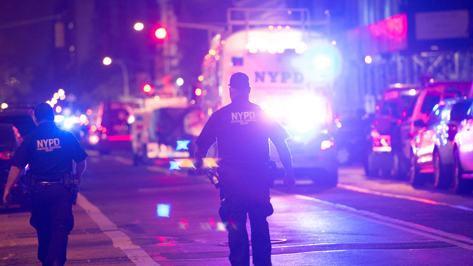 Police and first responders walk down a blocked off road near the site of an alleged bomb explosion on West 23rd Street on September 17, 2016, in New York. An explosion in New York's upscale and bustling Chelsea neighborhood injured at least 25 people, none of them in a life-threatening condition, late Saturday, the fire department said.