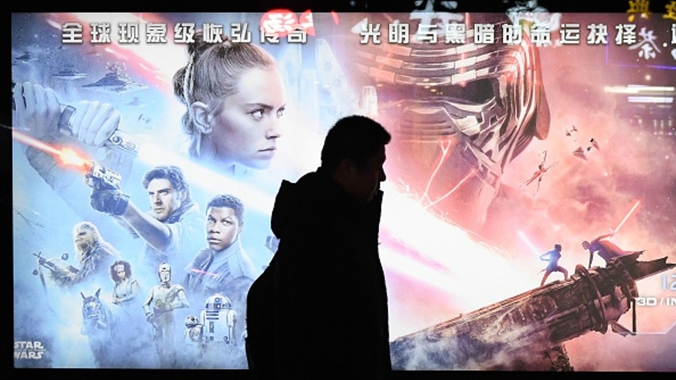 """This photo taken on December 19, 2019 shows a man walking past a poster for the latest Star Wars movie, """"The Rise of Skywalker"""", in Beijing. - The movie opens in theaters in China on December 20."""