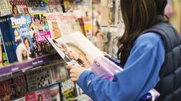 Woman reading gossip magazine at a news stand. (Photo by John Greim/LightRocket via Getty Images)