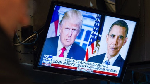 US President Donald Trump and former President Barack Obama potraits are on television as traders work on the floor at the closing bell of the Dow Industrial Average at the New York Stock Exchange on May 8, 2018 in New York. - Wall Street stocks finished essentially flat Tuesday as investors tried to assess the potential fallout from US President Donald Trump's decision to pull the US out of the Iran nuclear accord. The Dow Jones Industrial Average ended the session 24,360.21, just a hair above Monday's close. (Photo by Bryan R. Smith / AFP)