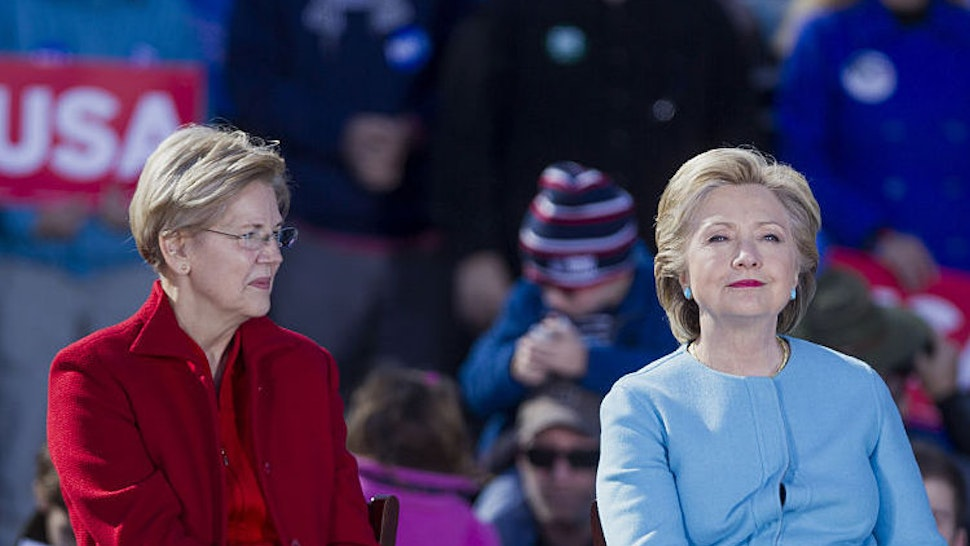 Senator Elizabeth Warren, a Democrat from Massachusetts, left, and Hillary Clinton, 2016 Democratic presidential nominee, sit on stage during a campaign event in Manchester, New Hampshire, U.S., on Monday, Oct. 24, 2016. Clinton made the case for herself in the presidential race against Donald Trump during rallies in Pennsylvania, and in a sign of her campaign's increasing outreach, also made a pitch for the efforts by Democrats to gain control of the Senate.