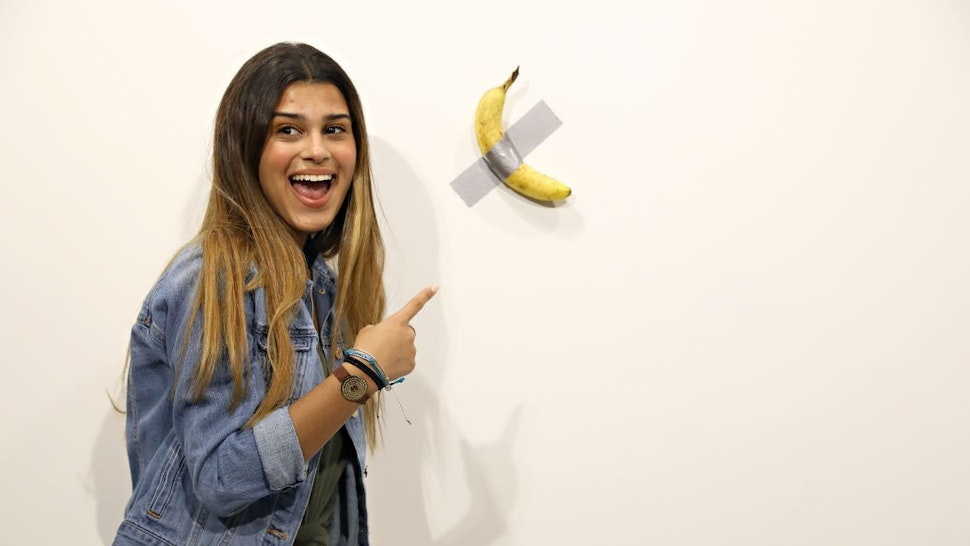 """People post in front of Maurizio Cattelan's """"Comedian"""" presented by Perrotin Gallery and on view at Art Basel Miami 2019 at Miami Beach Convention Center on December 6, 2019 in Miami Beach, Florida. Two of the three editions of the piece, which feature a banana duct-taped to a wall, have reportedly sold for $120,000."""