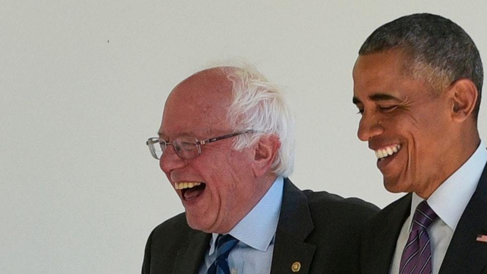 US President Barack Obama (R) walks with Democratic presidential candidate Bernie Sanders through the Colonnade for a meeting in the Oval Office on June 9, 2016 at the White House in Washington, DC.