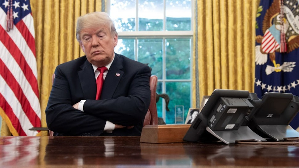 US President Donald Trump sits at the Resolute Desk during a briefing on Hurricane Michael in the Oval Office of the White House in Washington, DC, October 10, 2018.