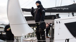 """Swedish climate activist Greta Thunberg waves from aboard the catamaran La Vagabonde as she sets sail to Europe in Hampton, Virginia, on November 13, 2019. - """"Extremely educational"""" is how Greta Thunberg sums up her North American sojourn as she prepares to cross the Atlantic once more, this time bound back for Europe. The 16-year-old Swede, who became world famous for founding the """"school strikes for the climate,"""" will set sail Wednesday morning, weather permitting, after 11 hectic weeks of criss-crossing the US and Canada, making headlines at every turn."""