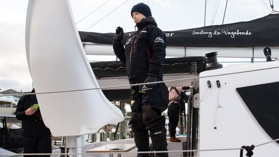 "Swedish climate activist Greta Thunberg waves from aboard the catamaran La Vagabonde as she sets sail to Europe in Hampton, Virginia, on November 13, 2019. - ""Extremely educational"" is how Greta Thunberg sums up her North American sojourn as she prepares to cross the Atlantic once more, this time bound back for Europe. The 16-year-old Swede, who became world famous for founding the ""school strikes for the climate,"" will set sail Wednesday morning, weather permitting, after 11 hectic weeks of criss-crossing the US and Canada, making headlines at every turn."