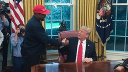 """(Files) in this file photo US President Donald Trump meets with rapper Kanye West in the Oval Office of the White House in Washington, DC, October 11, 2018. - Rapper Kanye West, who has been outspoken in his support for President Donald Trump, now says he's going to focus on his music and fashion after being """"used"""" in the world of politics, October 30, 2018."""