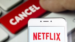 In this photo illustration a American global on-demand Internet streaming media provider Netflix logo is seen on an Android mobile device with a computer key which says cancel.