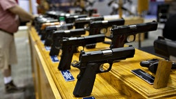 A worker sets up a display of handguns on the floor of the exhibition hall ahead of the National Rifle Association (NRA) annual meeting at the Indiana Convention Center in Indianapolis, Indiana, U.S., on Thursday, April 25, 2019. President Donald Trump will speak at the NRA Institute for Legislative Action (NRA-ILA) Leadership Forum on Friday.