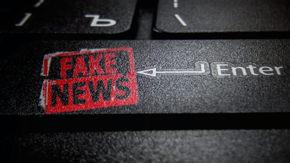 In this photo illustration a fake news logo and a laptop keyboard.