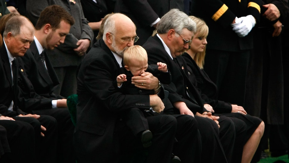 ARLINGTON, WA - APRIL 08: Peter Hake comforts his 18-month old grandson Gage during the burial service for his son, Army SSG Christopher M. Hake, at Arlington National Cemetery April 8, 2008 in Arlington, Virginia.