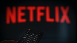 A remote control is seen being held in front of a television running the Netflix application on October 25, 2017.