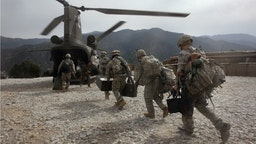 U.S. soldiers board an Army Chinook transport helicopter after it brought fresh soldiers and supplies to the Korengal Outpost on October 27, 2008 in the Korengal Valley, Afghanistan.