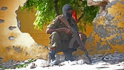 A Somali soldier stands guard next to the site where Al Shebab militants carried out a suicide attack against a military intelligence base in Mogadishu on June 21, 2015. Shebab militants launched a major suicide raid on June 21 against a military intelligence base in the capital Mogadishu, setting off a car bomb before storming inside, security officials said. Somalia's interior ministry said the three attackers were all killed in the raid, and that Somali security forces who fought them suffered no casualties.