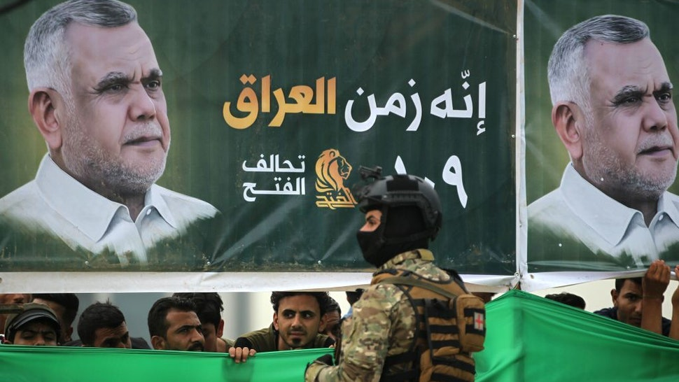 Iraqi supporters of the Fateh Alliance, a coalition of Iranian-supported militia groups, listen to a speech by Hadi Amiri (portrait), head of the Iranian-backed Badr Organization and leader of the Fateh Alliance, during a campaign rally in Baghdad on May 7, 2018, ahead of Iraq's parliamentary elections to be held on May 12. (Photo by AHMAD AL-RUBAYE / AFP) (Photo credit should read AHMAD AL-RUBAYE/AFP via Getty Images)