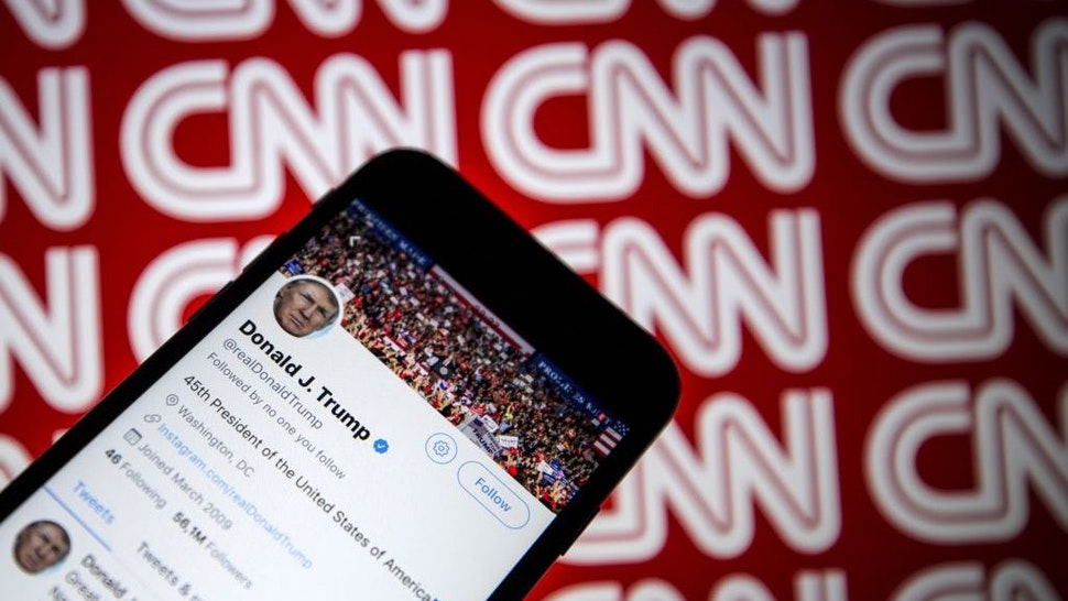 Donald Trump's Twitter profile is seen on a smartphone against a backdrop with the CNN logo, in Ankara, Turkey on December 9, 2018. (Photo by Ali Balkci/Anadolu Agency/Getty Images)
