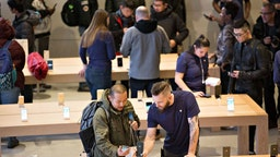 Employees assist customers with Apple Inc. iPhone X smartphones during the sales launch at a store in Chicago, Illinois, U.S., on Friday, Nov. 3, 2017. The $1,000 price tag on Apple Inc.'s new iPhone X didn't deter throngs of enthusiasts around the world who waited -- sometimes overnight -- in long lines with no guarantee they would walk out of the store with one of the coveted devices.