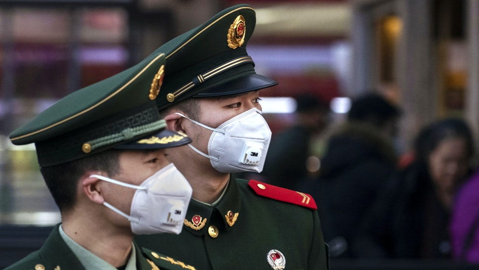 BEIJING, CHINA - JANUARY 22: Chinese police officers wear protective masks at Beijing Station before the annual Spring Festival on January 22, 2020 in Beijing, China. The number of cases of a deadly new coronavirus rose to over 400 in mainland China Wednesday as health officials stepped up efforts to contain the spread of the pneumonia-like disease which medicals experts confirmed can be passed from human to human. The number of those who have died from the virus in China climbed to nine on Wednesday and cases have been reported in other countries including the United States,Thailand, Japan, Taiwan and South Korea.
