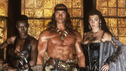 Austrian-born American actor, producer and politician Arnold Schwarzenegger, Jamaican singer, actress and model Grace Jones and British actress Sarah Douglas looking into the camera in the film Conan the Destroyer. Mexico, 1984 (Photo by Mondadori via Getty Images)
