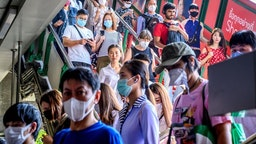 People with face masks arrive at a BTS Sky train station in Bangkok on January 27, 2020. - Thailand has detected eight Coronavirus cases so far -- three of whom are receiving treatment in hospital and five of whom have been discharged, according to a statement from Health Minister Anutin Charnvirakul. (Photo by Mladen ANTONOV / AFP) (Photo by MLADEN ANTONOV/AFP via Getty Images)