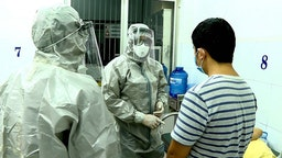Medical personnel wearing protectice suits interact with two patients (R on bed and standing) tested positive to the coronavirus in an isolation room at Cho Ray hospital in Ho Chi Minh City on January 23, 2020. - Two Chinese nationals in Vietnam have tested positive for the SARS-like coronavirus and are being treated in hospital, officials said on January 23. (Photo by STR / Vietnam News Agency / AFP)