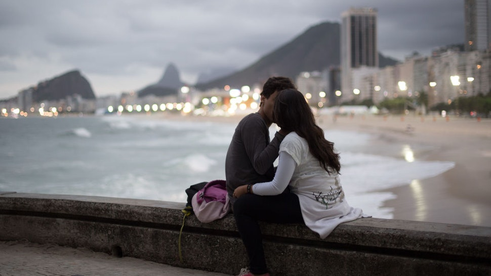 A couple kisses at Copacabana beach in Rio de Janiero, Brazil, August 03, 2016.