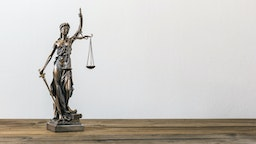 Close-Up Of Lady Justice On Table Against Wall - stock photo