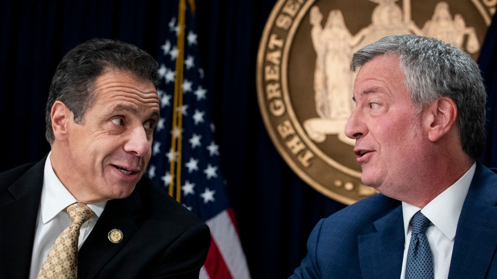 New York Governor Andrew Cuomo and New York City Mayor Bill de Blasio talk with each other during a press conference to discuss Amazon's decision to bring a new corporate location to New York City, November 13, 2018 in New York City.