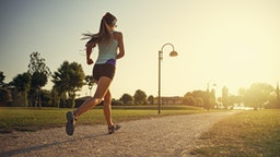 Teenage girl jogging in city park - stock photo