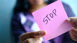 a young girl holding note pad with abuse text written