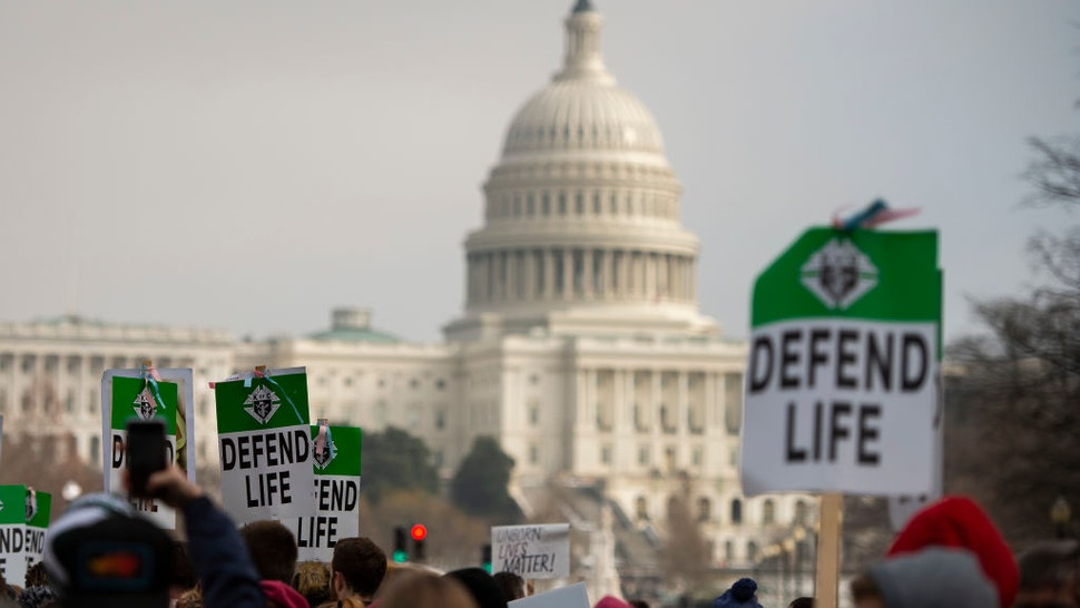 """Students and activists carry signs during the annual """"March for Life"""" in Washington, DC on January 18, 2019."""