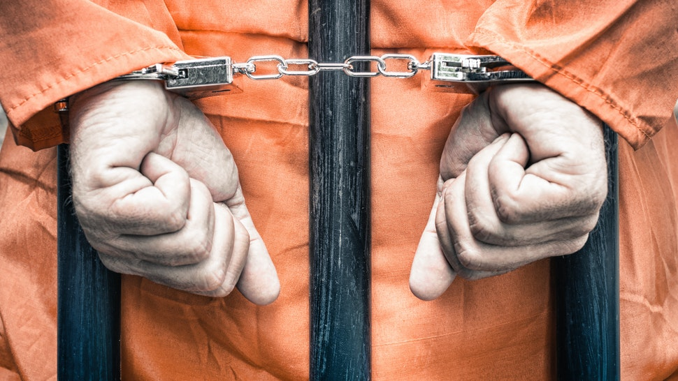 Close-Up Of Man With Handcuffs Standing In Prison - stock photo