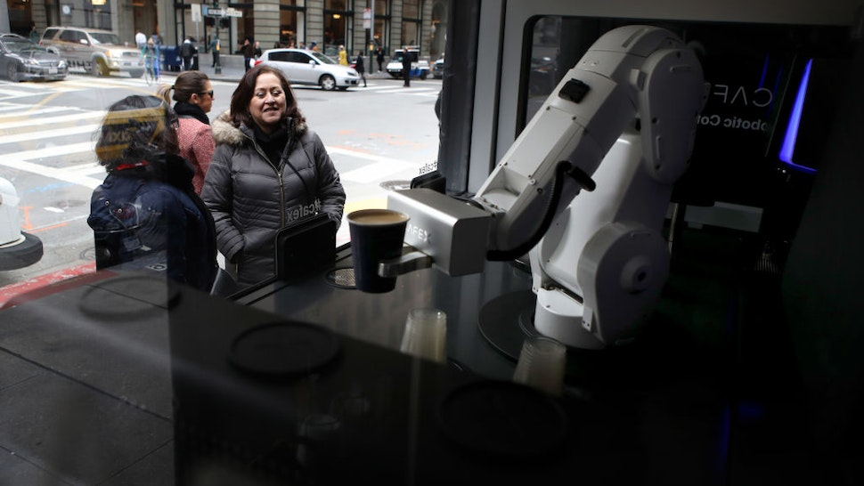 Customers watch as a robotic barista makes coffee drinks at Cafe X on February 12, 2019 in San Francisco, California. Cafe X is one of several food service companies that are using robots to serve food and beverages.