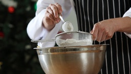 Midsection Of Chef Straining Flour In Bowl At Kitchen - stock photo