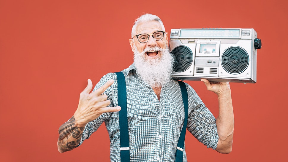Hipster Senior Man Listening Music On Radio Against Red Background - stock photo