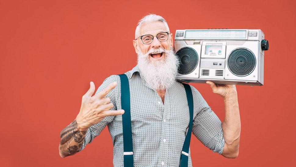 Hipster Senior Man Listening Music On Radio Against Red Background - stock photo