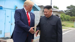 "PANMUNJOM, SOUTH KOREA - JUNE 30 (SOUTH KOREA OUT): A handout photo provided by Dong-A Ilbo of North Korean leader Kim Jong Un and U.S. President Donald Trump inside the demilitarized zone (DMZ) separating the South and North Korea on June 30, 2019 in Panmunjom, South Korea. U.S. President Donald Trump and North Korean leader Kim Jong-un briefly met at the Korean demilitarized zone (DMZ) on Sunday, with an intention to revitalize stalled nuclear talks and demonstrate the friendship between both countries. The encounter was the third time Trump and Kim have gotten together in person as both leaders have said they are committed to the ""complete denuclearization"" of the Korean peninsula. (Handout photo by Dong-A Ilbo via Getty Images/Getty Images)"