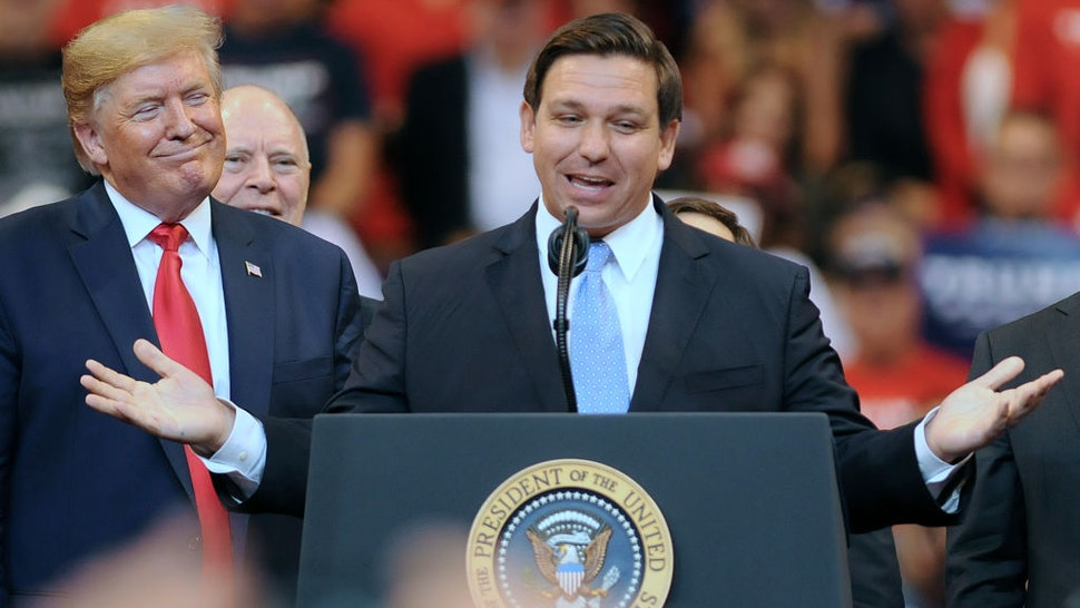 President Donald Trump looks on as Florida Governor Ron DeSantis speaks during the Florida Homecoming rally at the BB&T Center.