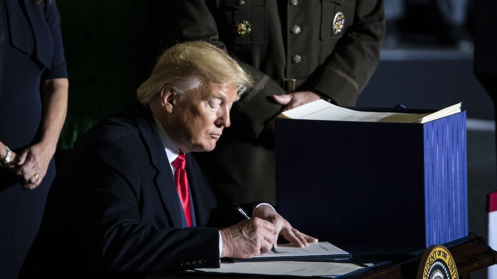 U.S. President Donald Trump signs the National Defense Authorization Act for Fiscal Year 2020 during a ceremony at Joint Base Andrews, Maryland, U.S., on Friday, Dec. 20, 2019.
