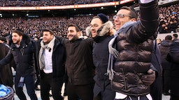 Men dance as they celebrate Siyum HaShas, the completion of the reading of the Babylonian Talmud, at the MetLife Stadium on January 1, 2020, in East Rutherford, New Jersey.