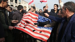 Iranians tear up a US flag during a demonstration in Tehran on January 3, 2020 following the killing of Iranian Revolutionary Guards Major General Qasem Soleimani in a US strike on his convoy at Baghdad international airport.